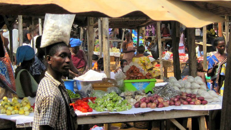 A man at the market in Sogakope, balancing a bag on his head.