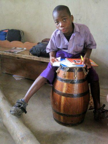 Using a drum as a makeshift desk in Ghana.