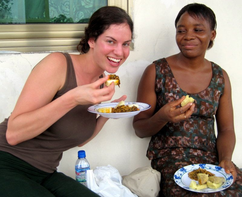 Scarfing delicious food in Ghana as Millicent chuckles.