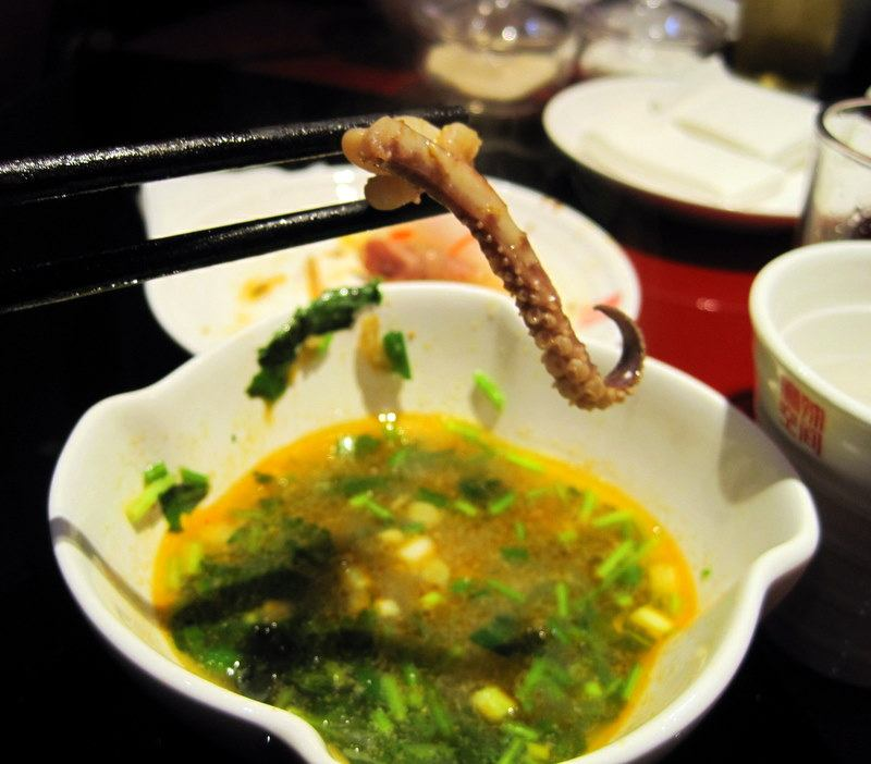 Dipping squid in oil during Hot Pot.