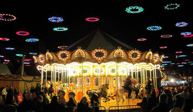 The carousel in Madrid's Plaza Mayor spins gold under rainbow circle lights for the holidays!