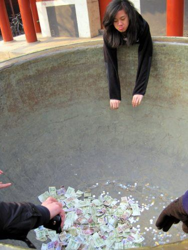Aww, poor thing can't reach the money pot at Lama Temple!