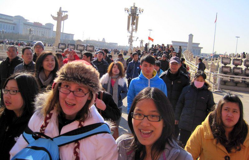 Candace on the crowded bridge from Tienanmen Square to the Forbidden City. Notice the face mask and surveillance cameras in back.