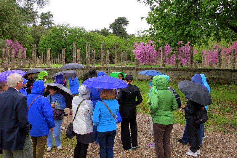 Our teacher tour group, huddled in the magic rain by Olympia's flowers.