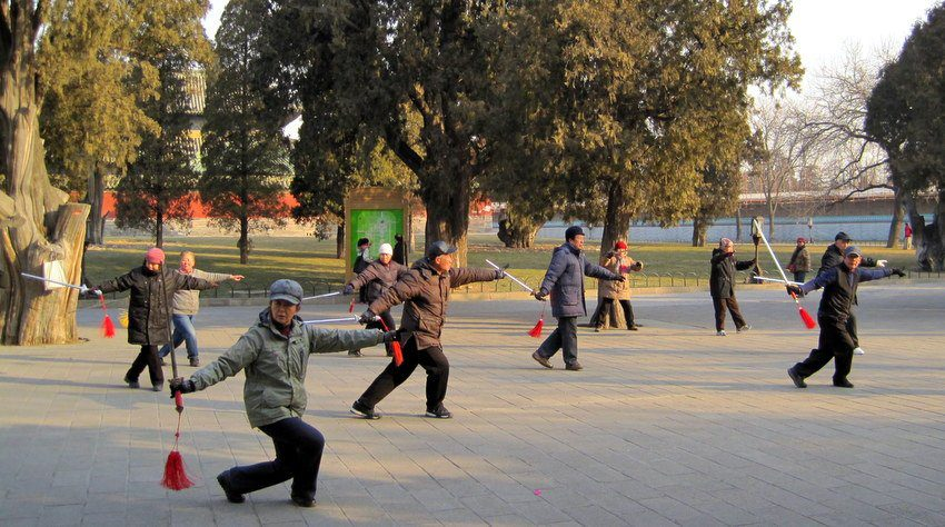People of all ages exercising (with swords!) in a Beijing park.
