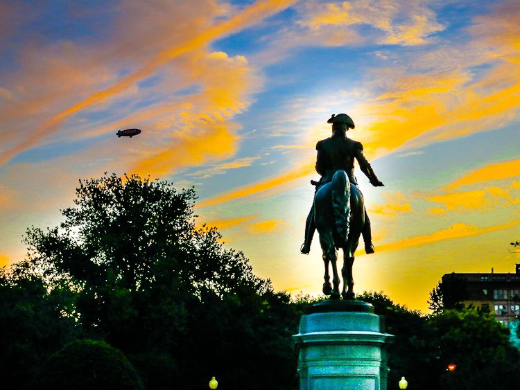 George Washington guards the Boston Public Garden entrance and watches the blimp in the pink sky.