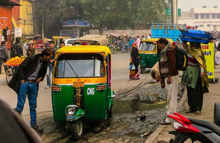 A couple carries their suitcases on their head as they hail an auto rickshaw by the Railway Station.