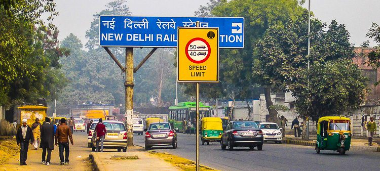 Cars, auto rickshaws, and pedestrians meet in New Delhi.