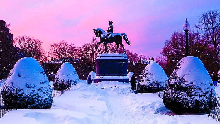 Boston Public Garden under two feet of snow with a sunset in back.