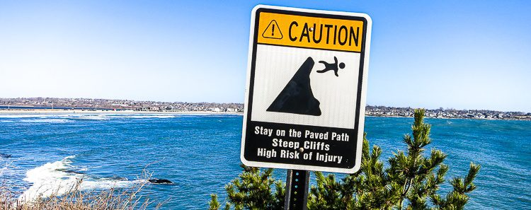 A warning sign on the Cliff Walk behind the mansions. When do we fall off the cliff of lavishness?