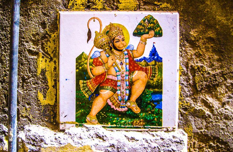 Why is it brilliant to hang this and other religious figures on an alley wall in India?