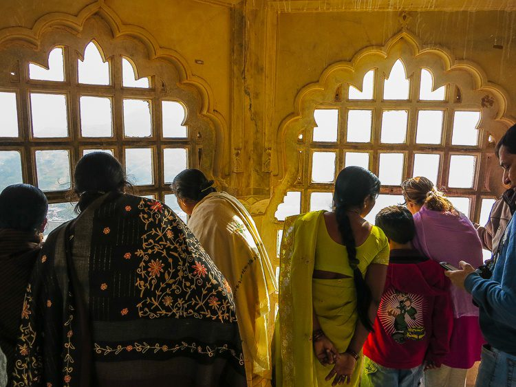 Women in saris looking out of a palace window.