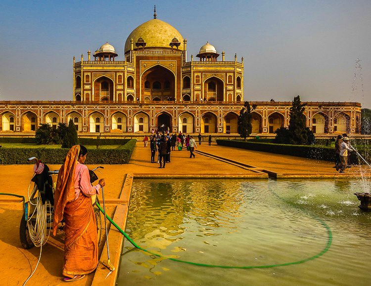"""A female worker cleaning the fountain at the """"Little Taj Mahal."""""""