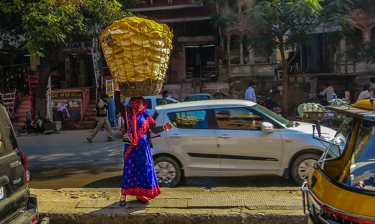 Selling a giant head-basket of bread by the roadside in a dreamy sari.