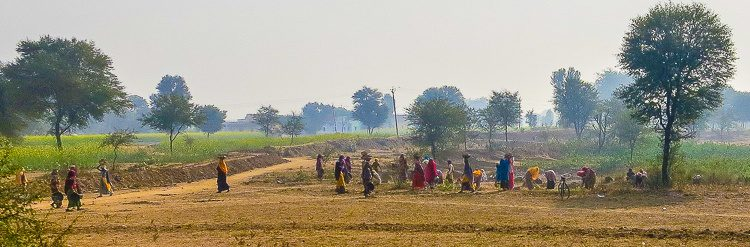 The bright clothing of agricultural workers glows through the haze.