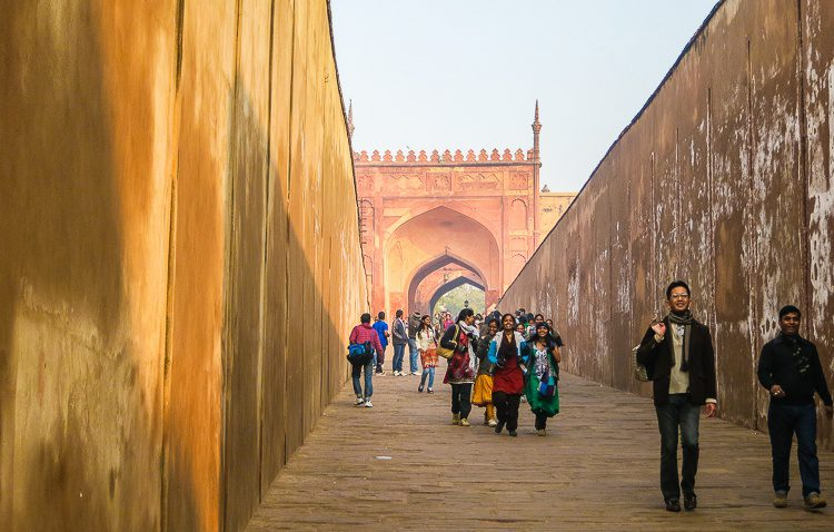 A pack of colorfully-dressed Indian students strides into Agra Fort.