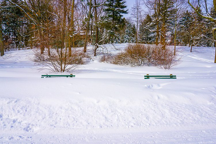 Two park benches completely submerged in snow.