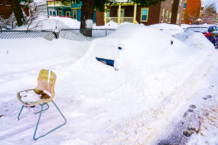 There's a car under all that snow on the right. On the left, someone is trying to reserve a shoveled spot.