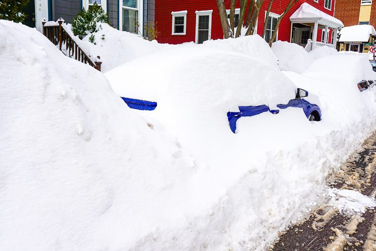 A blue car peeking out of the snow bank.