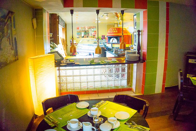 You can peek into the kitchen from this table at The Pins.