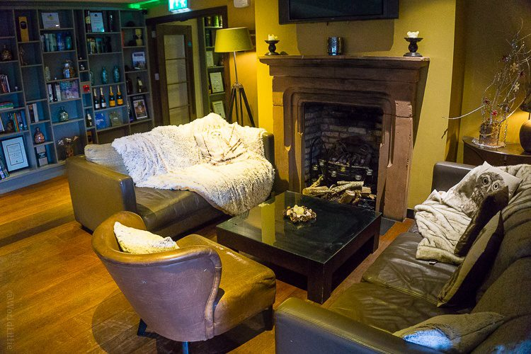 The fireplace and blanketed sofa you see walking into The Pins Gastropub.