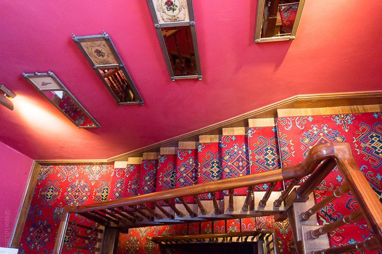 Bold red walls and ornate carpeting in the stairways.
