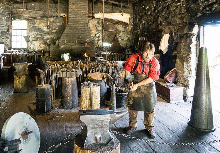 Old Sturbridge Village Blacksmith getting ready to hammer on an anvil.