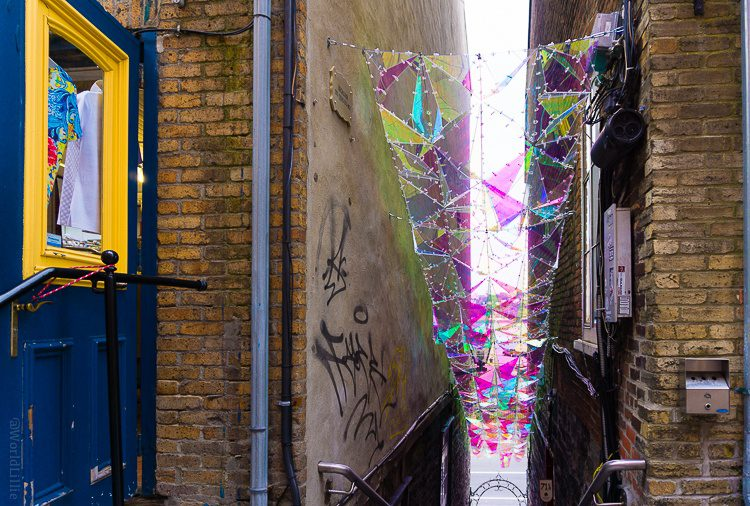Pink glass street art in an alley.