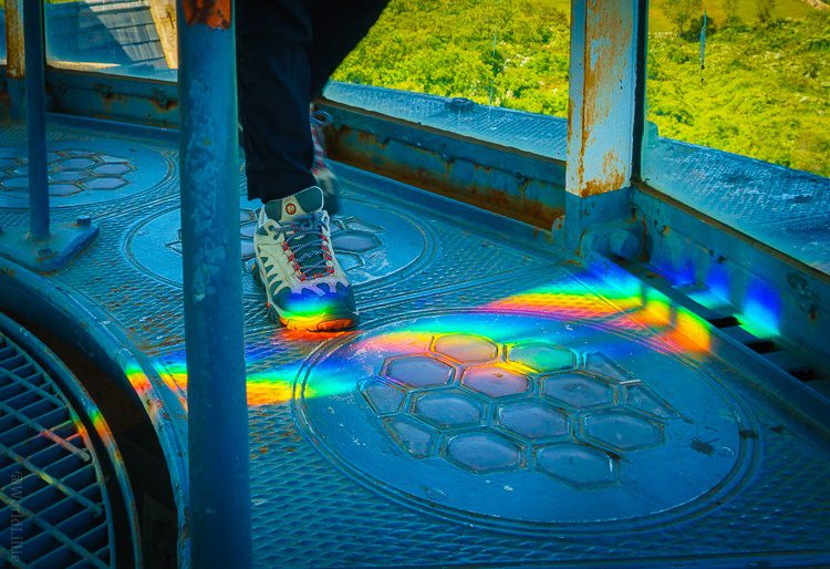 The lens of the light makes rainbows on the platform.