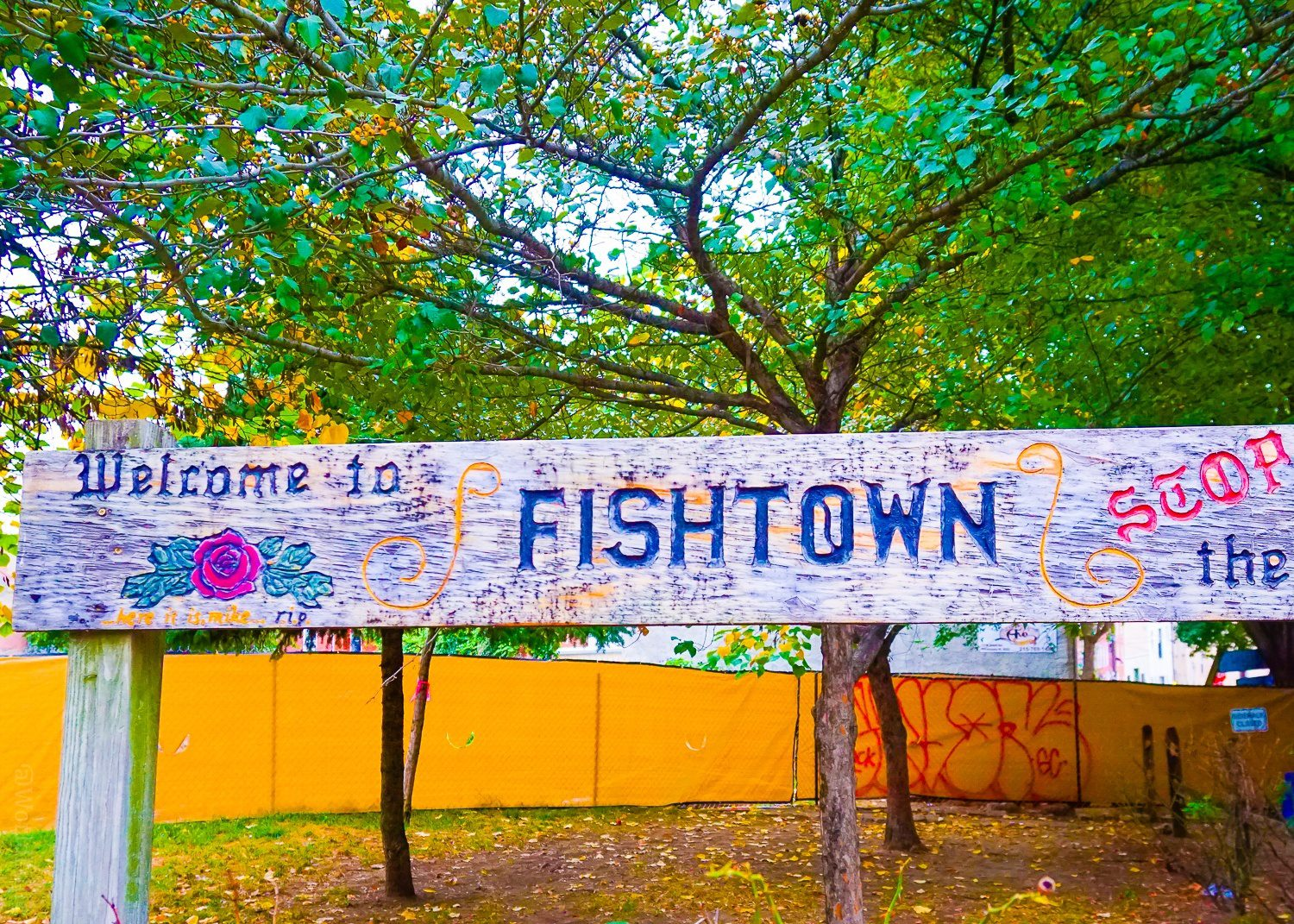 """The sign says, """"Fishtown: Stop and Smell the Roses."""""""