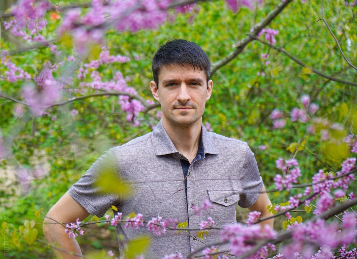 Peeking from behind a flower tree with a manly shirt.