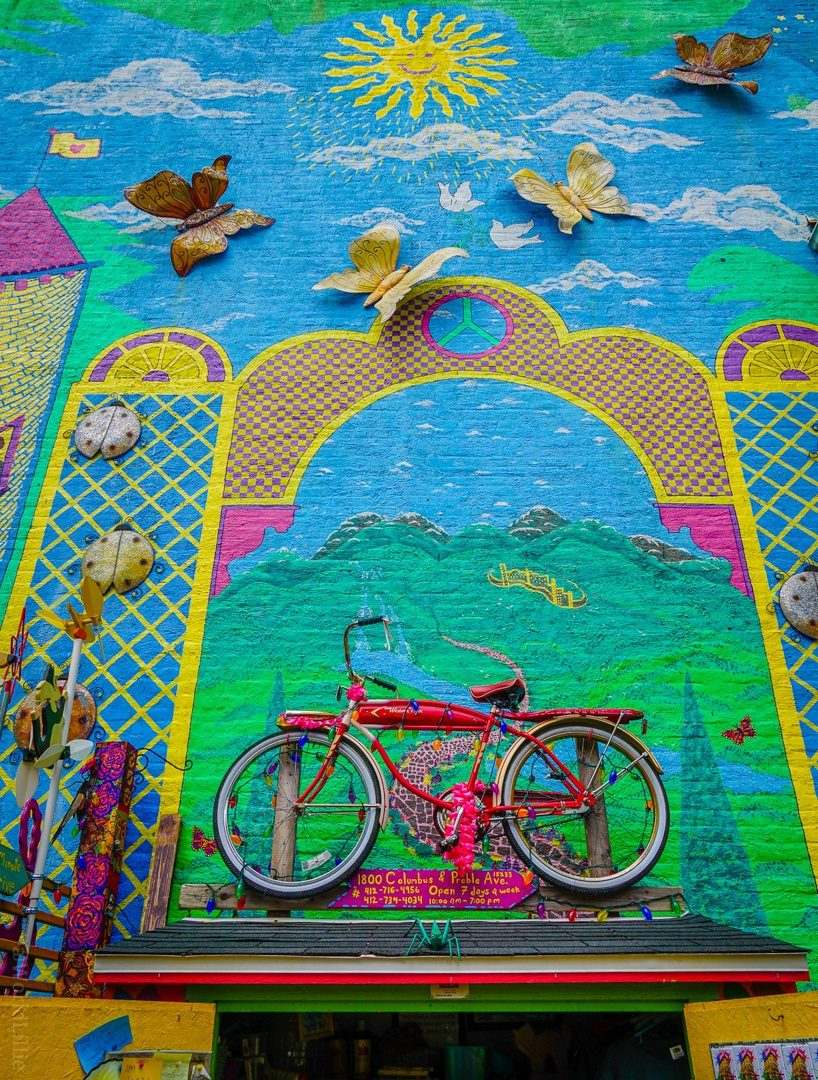 Bike on a wall? Why not? Randyland is the best free place to visit in Pittsburgh, PA for colorful photos, fun, & creative humor! See psychedelic rainbow photos from a visiting teacher. #Pittsburgh #Randyland #Travel #Color #Design #Creativity