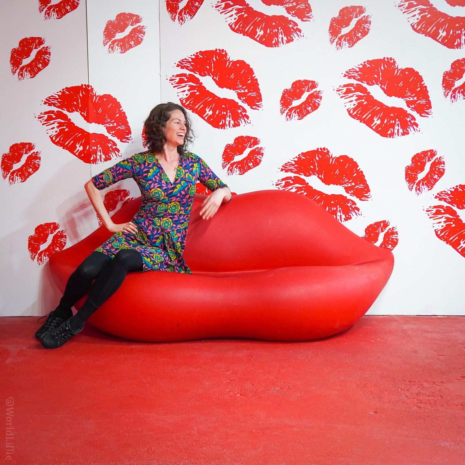 Happy Place: Sitting on a giant red lips couch with lipstick kisses on the wall.