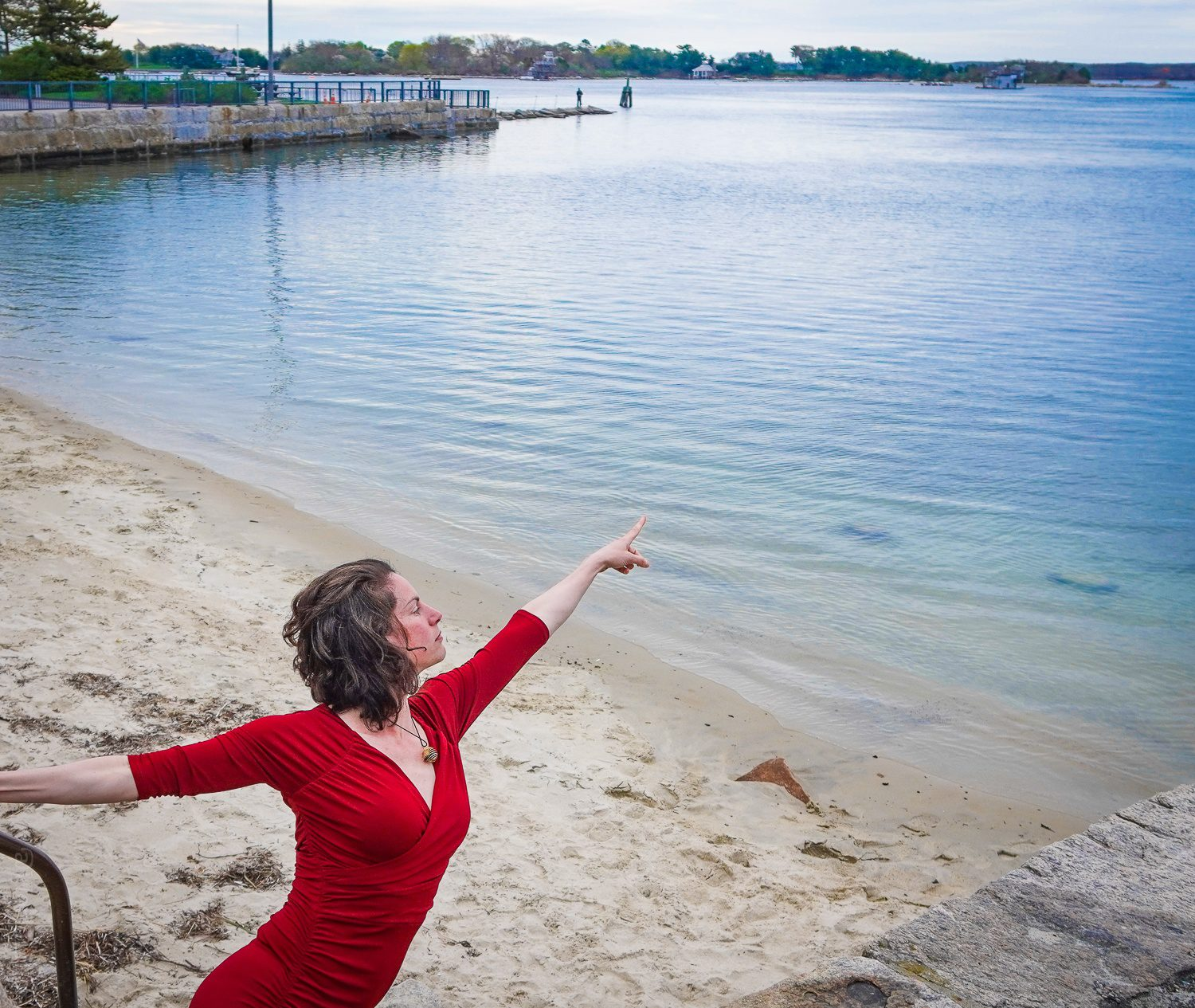 Pointing at Woods Hole beach in a red dress