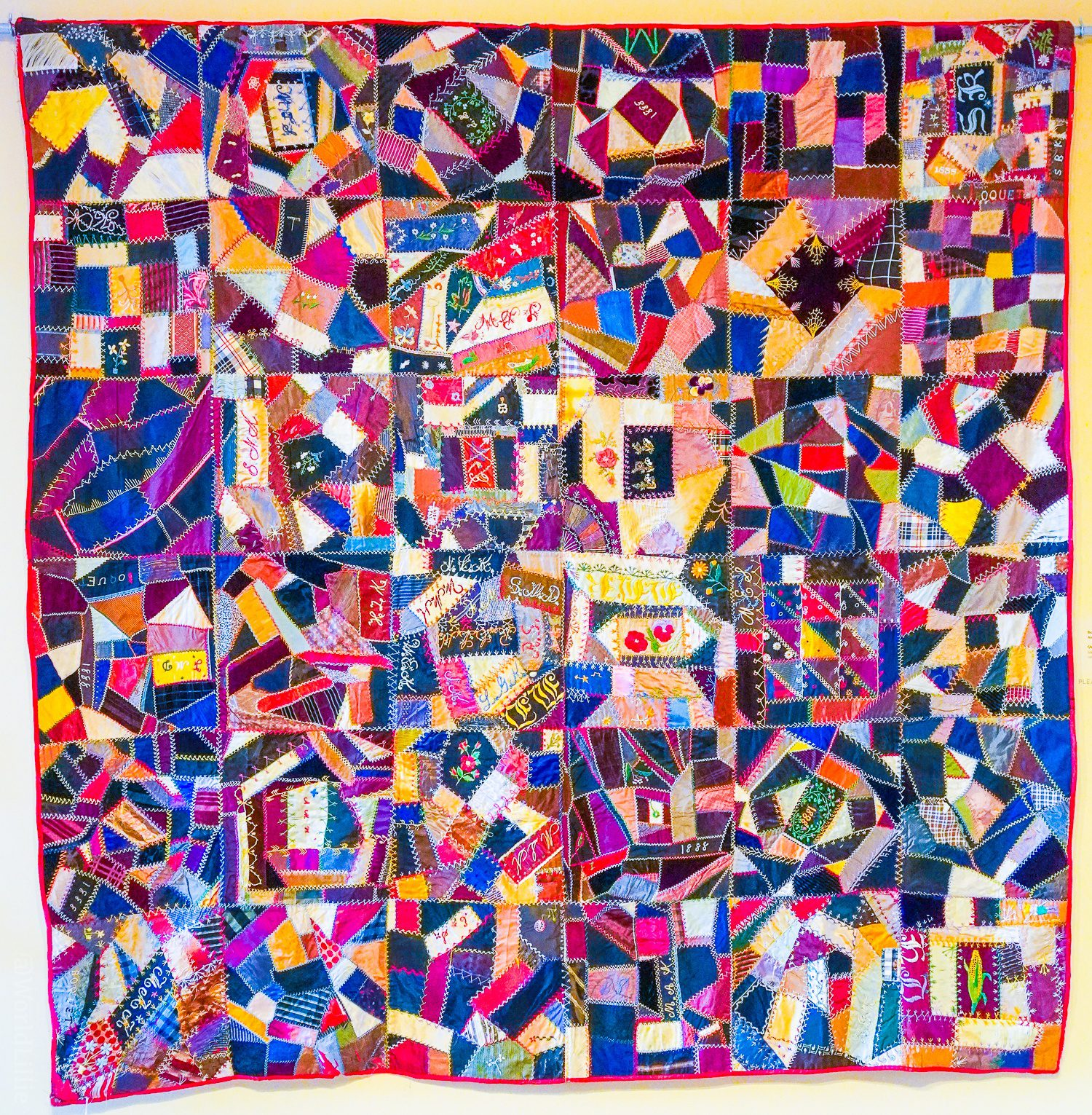 An ornate hand-sewn quilt near the room of drawers.