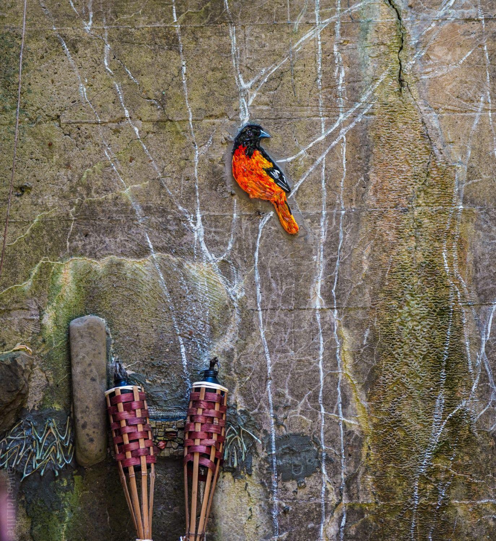 Bright orange mosaic bird amid the ruins.